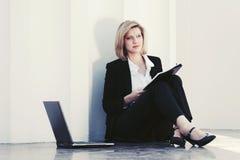 Junge Geschäftsfrau mit dem Laptop, der am Bürogebäude sitzt Lizenzfreie Stockfotos