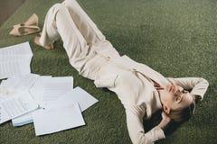 Junge Geschäftsfrau mit den geschlossenen Augen, die im Büro liegen und stillstehen Stockfoto