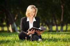 Junge Geschäftsfrau mit einem Ordner auf Natur Stockfoto