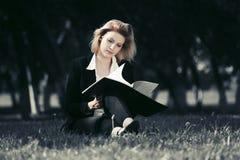 Junge Geschäftsfrau mit einem Ordner in einem Stadtpark Lizenzfreies Stockbild