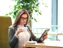 Junge Geschäftsfrau mit einem Tasse Kaffee, der im Büro arbeitet stockfotografie