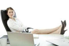 Junge Geschäftsfrau mit Füßen auf Schreibtisch lizenzfreie stockfotos