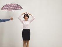 Junge Geschäftsfrau mit ihrer Hand über Kopf, Mitarbeiter, der ihren Regenschirm gibt Lizenzfreie Stockbilder