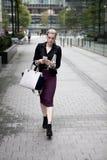 Junge Geschäftsfrau mit intelligentem Telefon draußen gehend Lizenzfreie Stockfotos
