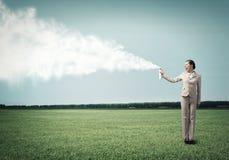 Junge Geschäftsfrau mit Koffer unter Verwendung des Sprays Stockfoto