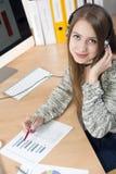 Junge Geschäftsfrau mit Kopfhörer an im Büro Lizenzfreie Stockfotos