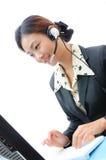 Junge Geschäftsfrau mit Kopfhörer und Computer Lizenzfreie Stockfotografie