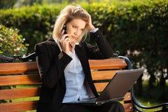 Junge Geschäftsfrau mit Laptop um Telefon ersuchend Stockfoto