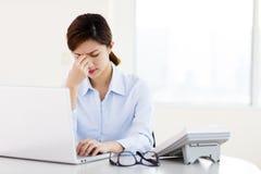 Junge Geschäftsfrau mit müden Augen und Kopfschmerzen lizenzfreie stockbilder