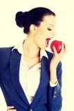 Junge Geschäftsfrau mit rotem Apfel Stockfoto
