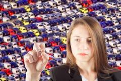 Junge Geschäftsfrau mit Stift in der Hand und viele Autos verwischt im Hintergrund Lizenzfreie Stockfotografie