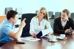 Junge Geschäftsfrau mit Teilhabern, Männer an einem Geschäft m Lizenzfreie Stockfotografie
