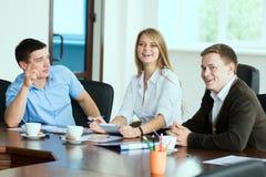 Junge Geschäftsfrau mit Teilhabern, Männer an einem Geschäft m Stockfoto