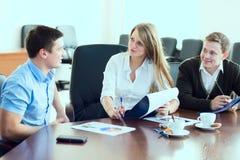 Junge Geschäftsfrau mit Teilhabern, Männer an einem Geschäft m Stockfotos