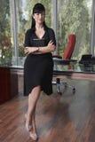 Junge Geschäftsfrau Sitting On Desk im Büro lizenzfreies stockfoto