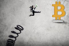 Junge Geschäftsfrau springen in Richtung zu bitcoin Symbol lizenzfreies stockfoto