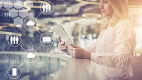 Junge Geschäftsfrau steht und benutzt Tablet-Computer Im Vordergrund sind virtuelle Ikonen mit Wolken, digitale Geräte Lizenzfreies Stockfoto