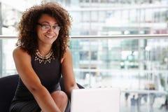 Junge Geschäftsfrau, welche die Laptop-Computer, schauend zur Kamera verwendet Stockfoto