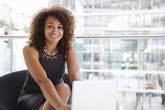 Junge Geschäftsfrau, welche die Laptop-Computer, schauend zur Kamera verwendet Lizenzfreie Stockfotografie