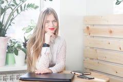 Junge Geschäftsfrau, welche die Zeit auf ihrer Uhr überprüft Stockfoto