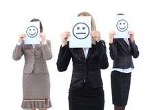 Junge Geschäftsfrauen, die hinter einem smileygesicht sich verstecken Stockbild