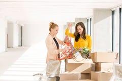 Junge Geschäftsfrauen, die Schnüre beim Bereitstehen von Pappschachteln im neuen Büro entwirren Stockfotos