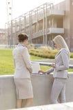 Junge Geschäftsfrauen, die zusammen an Laptop bei der Stellung gegen Bürogebäude arbeiten Stockbilder