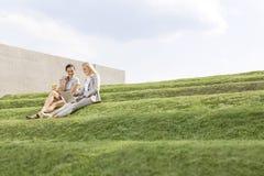 Junge Geschäftsfrauen, die zusammen Laptop verwenden, beim Sitzen auf Gras gegen Himmel tritt Lizenzfreies Stockfoto