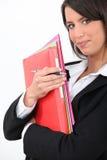 Junge Geschäftsfrauholdingfaltblätter lizenzfreie stockfotografie