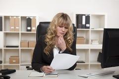 Junge Geschäftsfraulesung durch ein Dokument Stockbilder