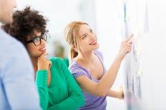 Junge Geschäftsleute besprechen Daten an Bord lizenzfreies stockfoto