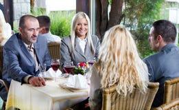 Junge Geschäftsleute an der Mittagessenrestaurantdiskussion lizenzfreies stockbild