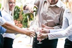Junge Geschäftsleute, die Champagner im Glas gießen Stockfotografie