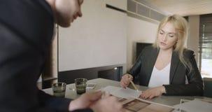 Junge Geschäftsleute, die Diskussion bei Tisch im Büro haben stock footage