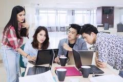 Junge Geschäftsleute, die im Büro sich besprechen stockfoto