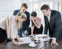 Junge Geschäftsleute, die am Konferenztische im Büro gedanklich lösen Stockfotos