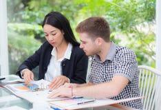 Junge Geschäftsleute, die Sitzung machen und Dokument nach dem Analysieren des Marketings arbeitet im Büro betrachten Stockfoto