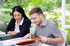 Junge Geschäftsleute, die Sitzung machen und Dokument nach dem Analysieren des Marketings arbeitet im Büro betrachten Lizenzfreie Stockbilder