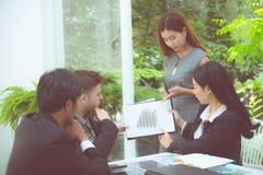 junge Geschäftsleute, die Sitzung machen und für das Analysieren des Marketings arbeitet im Büro auf Schreibtisch sprechen Stockfotos