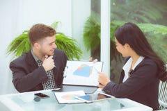 junge Geschäftsleute, die Sitzung machen und für das Analysieren des Marketings arbeitet im Büro auf Schreibtisch sprechen Lizenzfreie Stockfotos