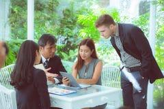 junge Geschäftsleute, die Sitzung machen und für das Analysieren des Marketings sprechen g m Stockbilder
