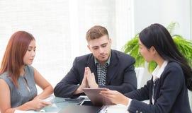 Junge Geschäftsleute, die Sitzung machen und Tablette nach dem Analysieren des Marketings arbeitet im Büro auf Schreibtisch betra Stockbilder