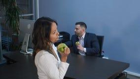 Junge Geschäftsleute, die zusammen, grünen Apfel essend zu Mittag essen stockbilder