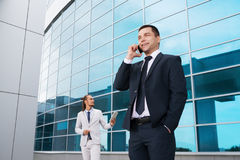 Junge Geschäftsmänner in den dunklen Anzügen und hell, lachend und freuen sich zu den Nachrichten empfangen durch den Handy Lizenzfreie Stockfotos