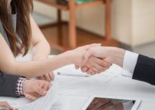 Junge Geschäftsmänner, die Hände mit einander im Geschäft rütteln Lizenzfreie Stockfotos