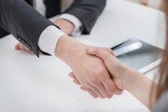 Junge Geschäftsmänner, die Hände mit einander im Geschäft rütteln Stockbild
