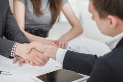 Junge Geschäftsmänner, die Hände mit einander im Geschäft rütteln Lizenzfreies Stockbild