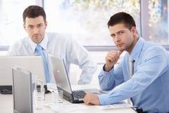 Junge Geschäftsmänner, die am Versammlungstisch arbeiten stockbilder