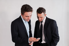 Junge Geschäftsmänner mit dem Smartphone auf einem weißen Hintergrund Lizenzfreie Stockfotografie