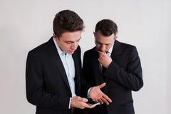 Junge Geschäftsmänner mit dem Smartphone auf einem weißen Hintergrund Lizenzfreie Stockfotos